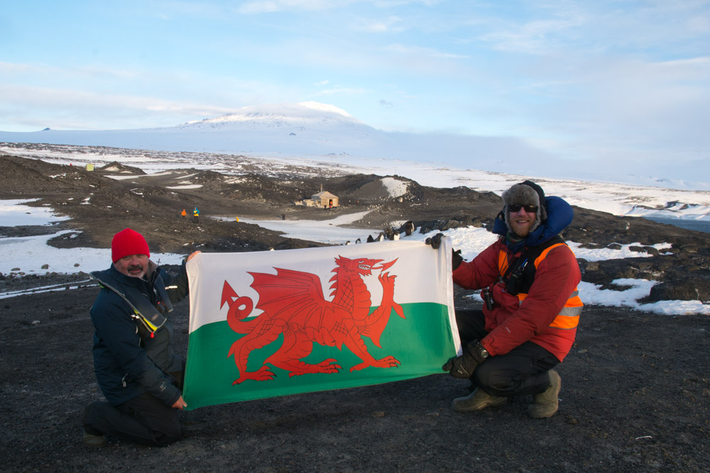 Myself, a friend and Welsh flag with Mount Erebus and Shackleton's hut, Cape Royds, Ross Island