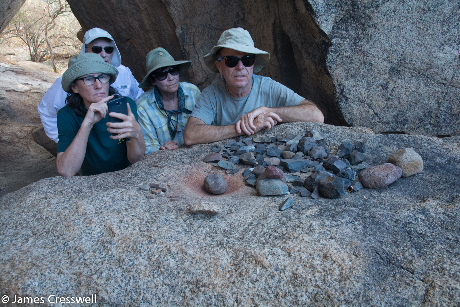 The GeoWorld Travel group observing where ochre was prepared for painting the prehistoric rock art, Erongo, Namibia.