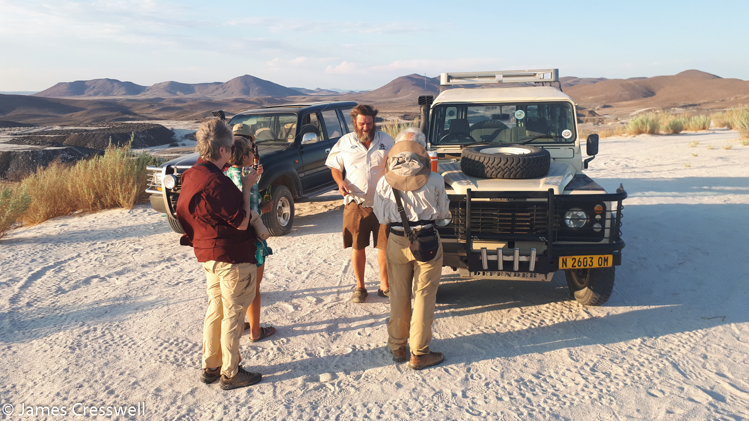The GeoWorld Travel group having a sundowner drink on a feldspar spoil heap above Uis Mine, Namibia.