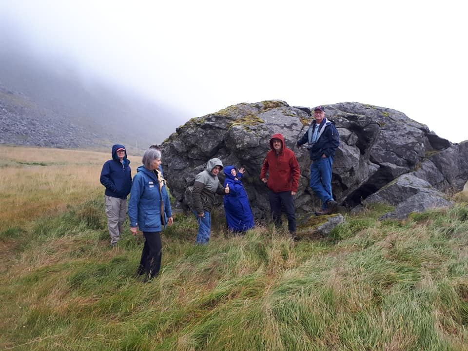Group standing by gabbro boulder