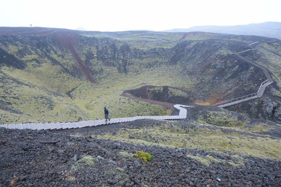 Person walking on path across a cinder cone