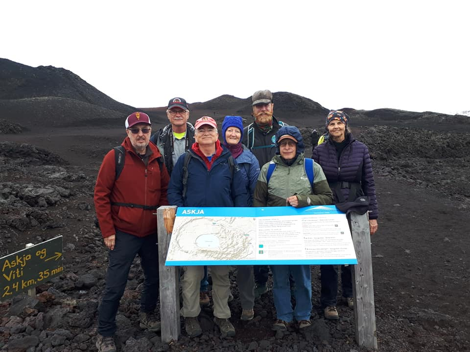 Group by signboard in volcanic landscape