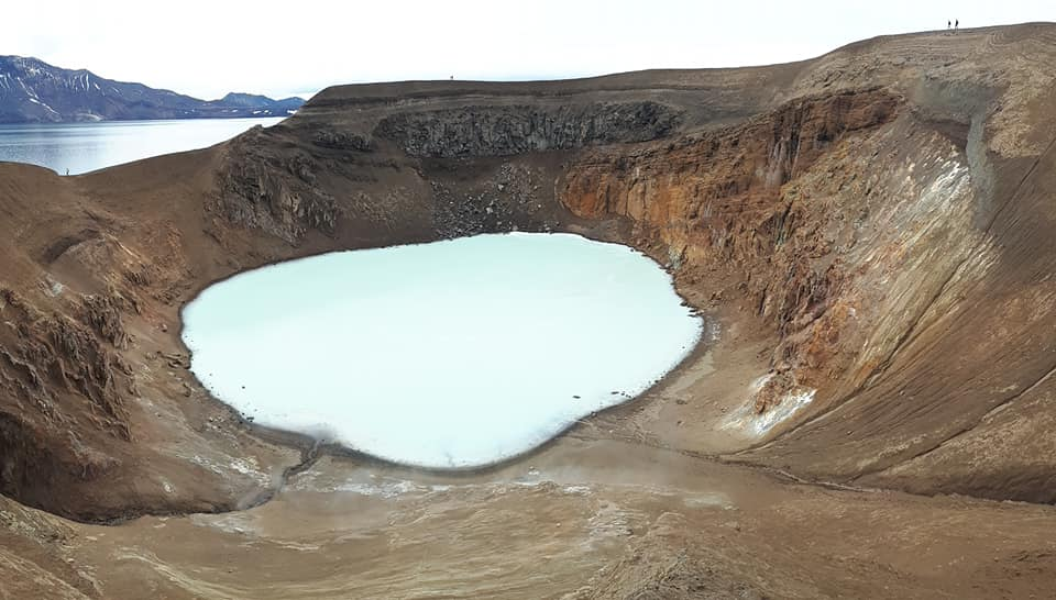Volcanic crater filled with pale blue water