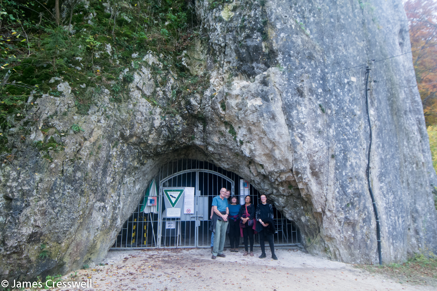 Group outside barred cave entrance