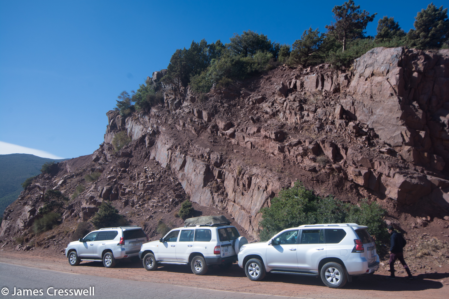 Vehicles at side of road in front of rock outcrop