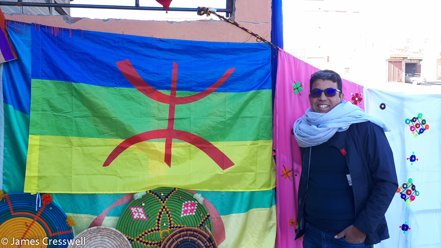 Man standing next to Berber flag