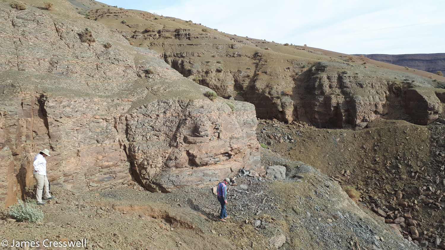 People by cliff with trilobite diggings