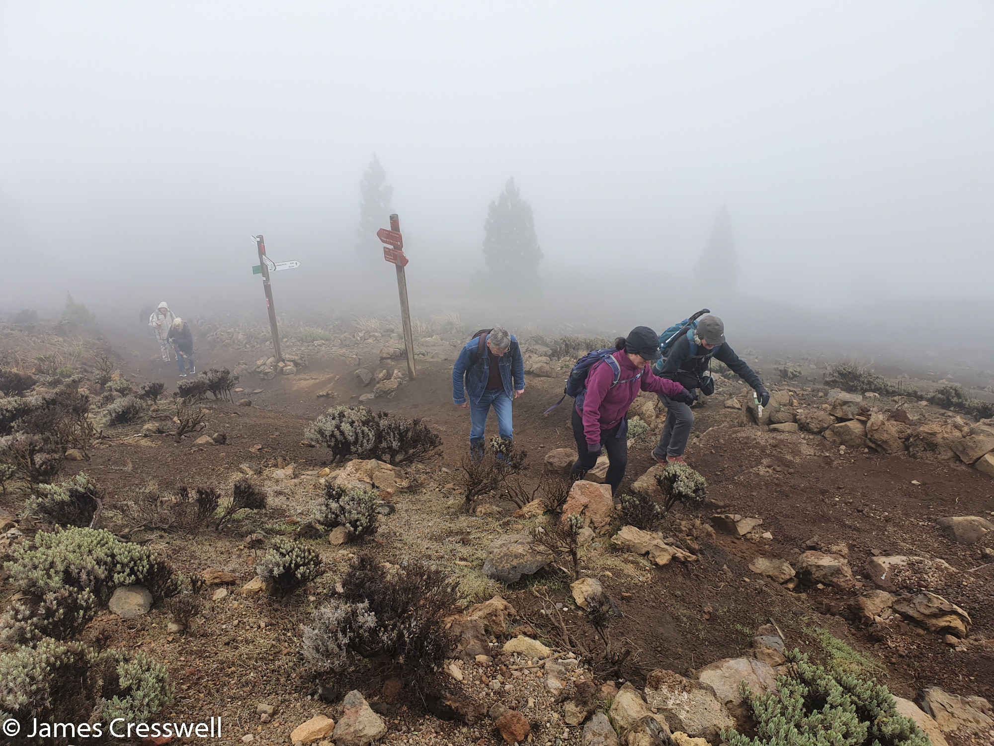 People climbing a rocky hill in cloudy conditions