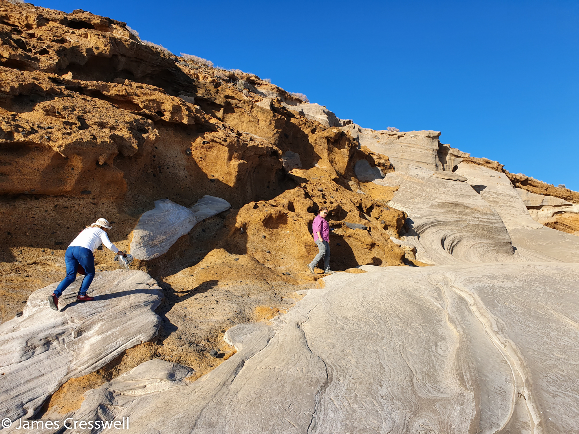 Two people walking across fossilised beach dunes