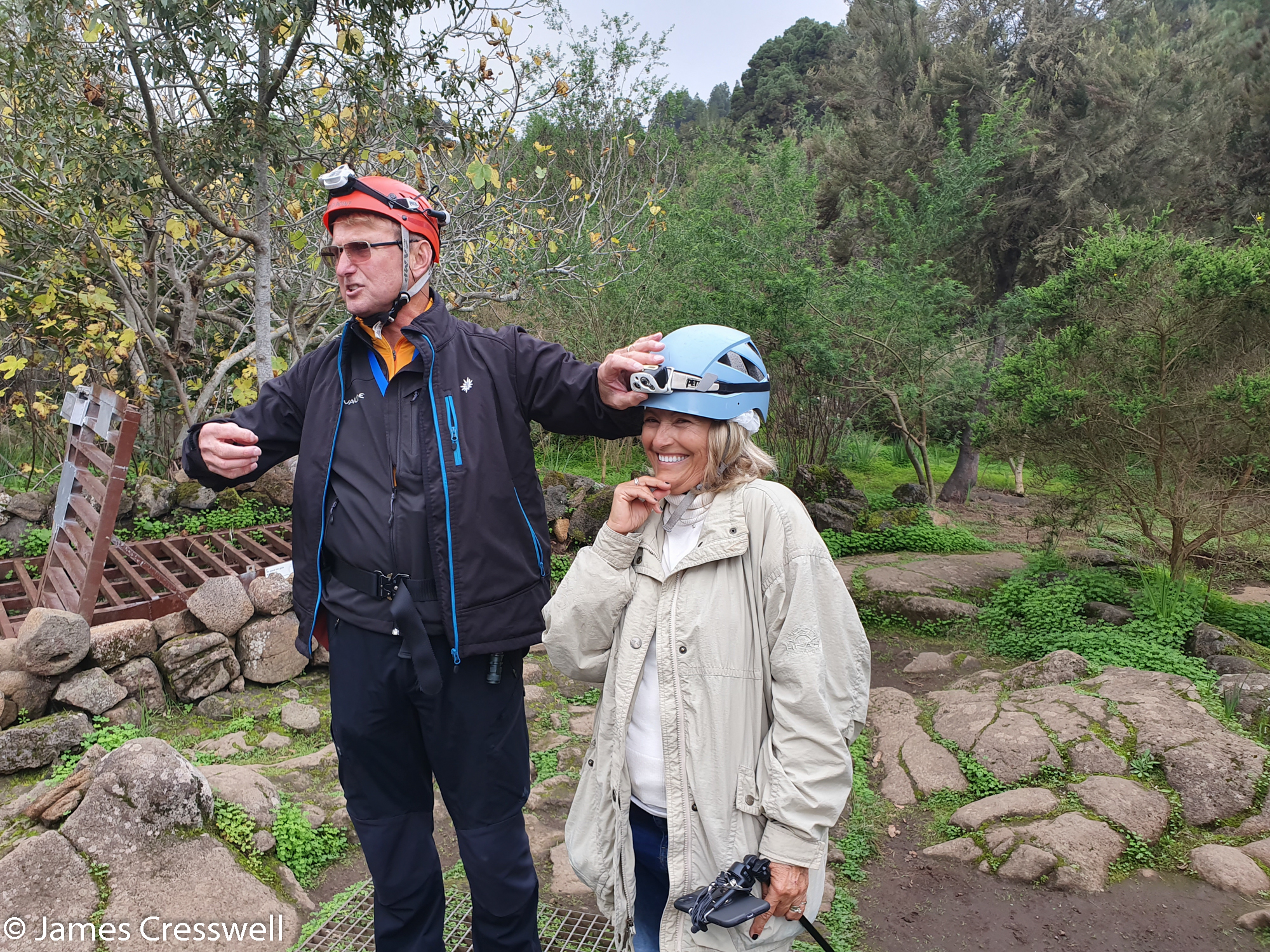 Man helping lady adjust her helmet light