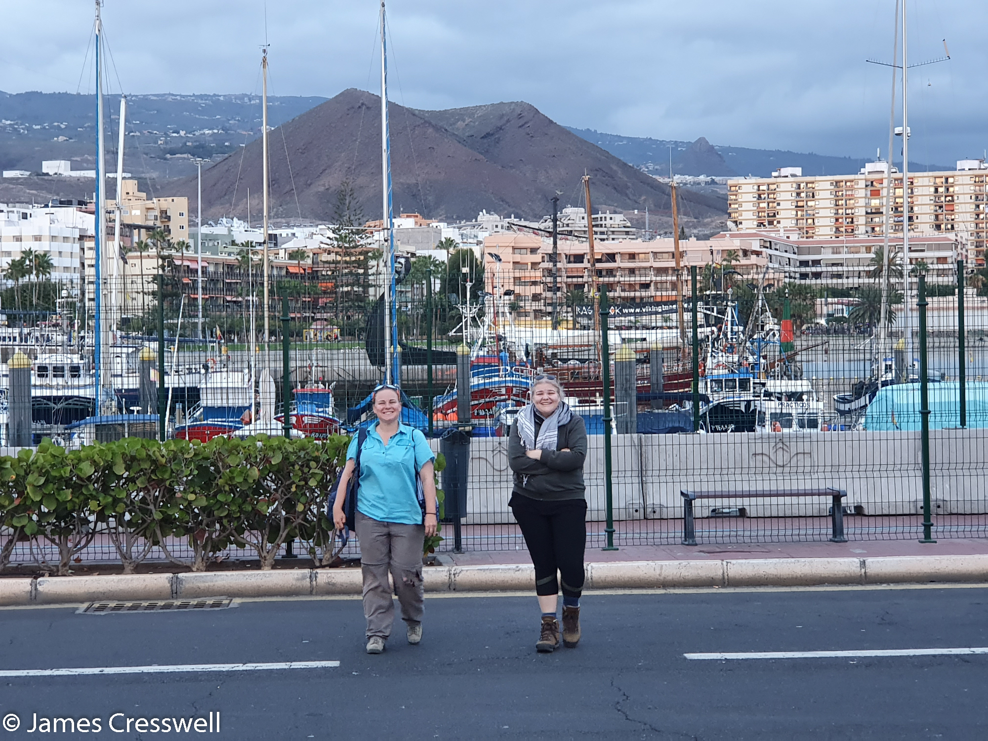 Two women crossing a road near a port with volanic feature behind