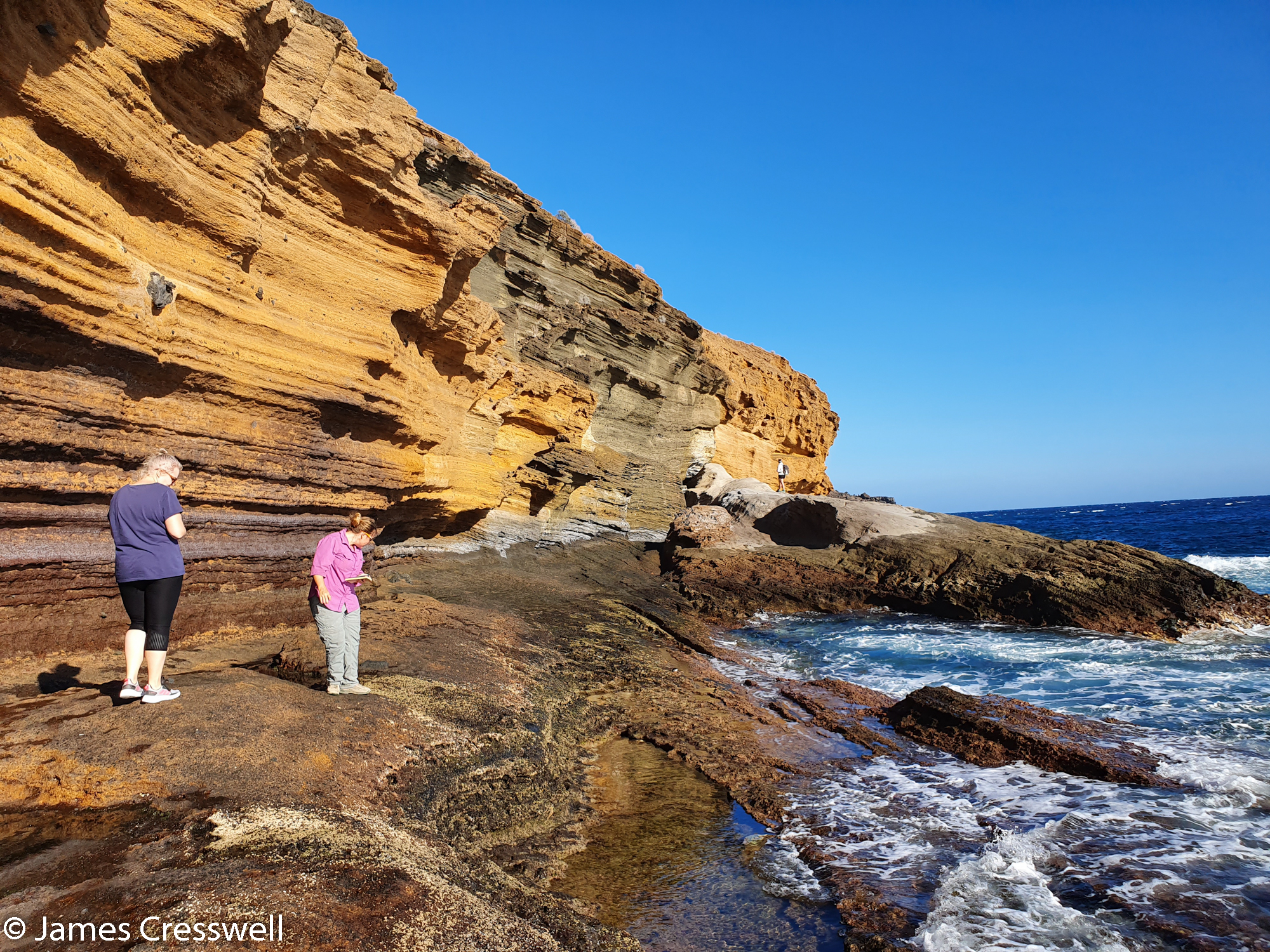 Two people looking at detail of coastal rock