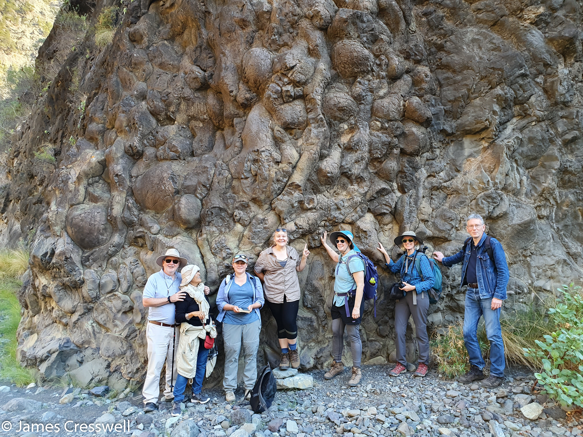 People standing in front of a rock face