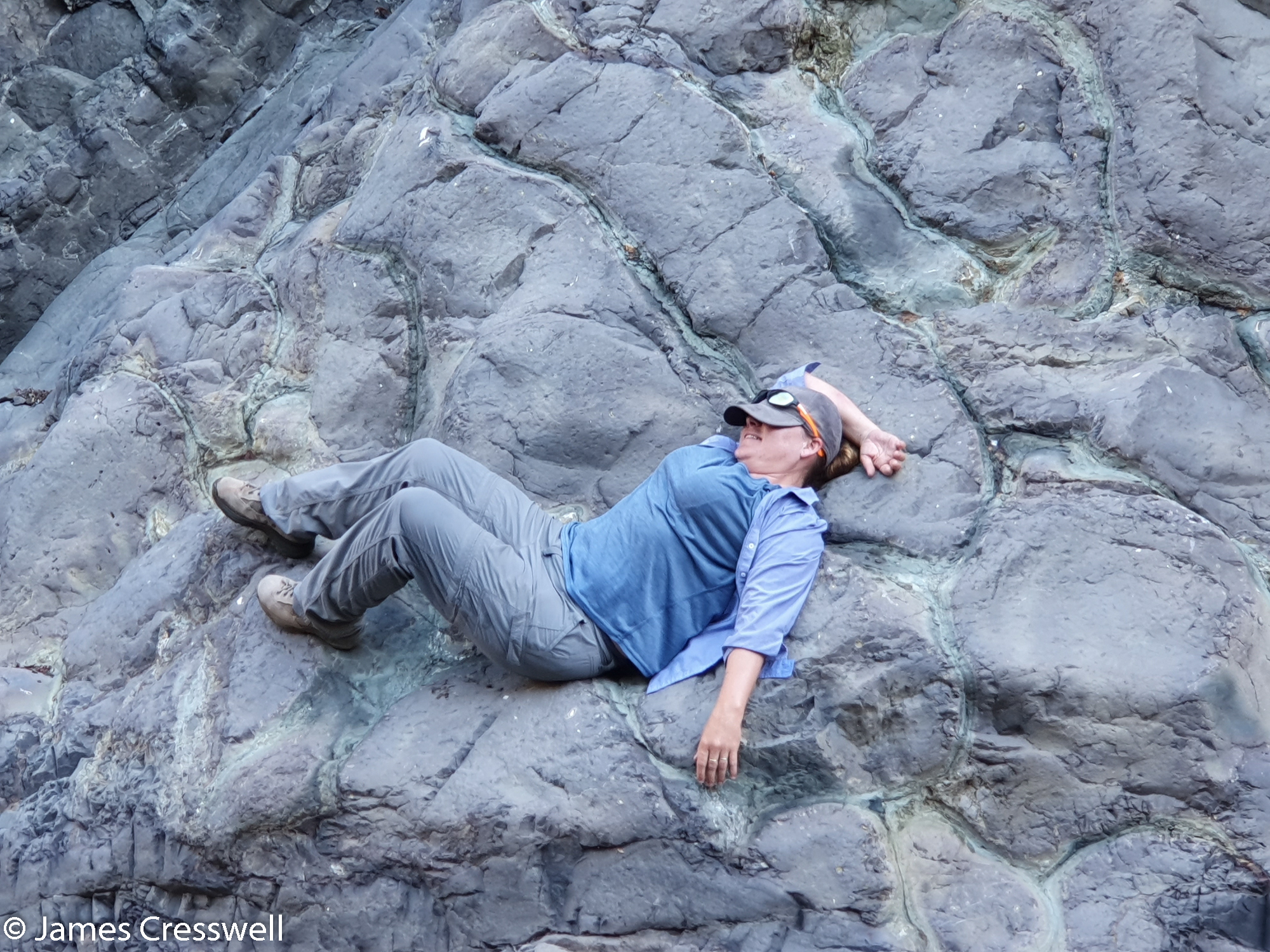 Woman lying on a rock outcrop