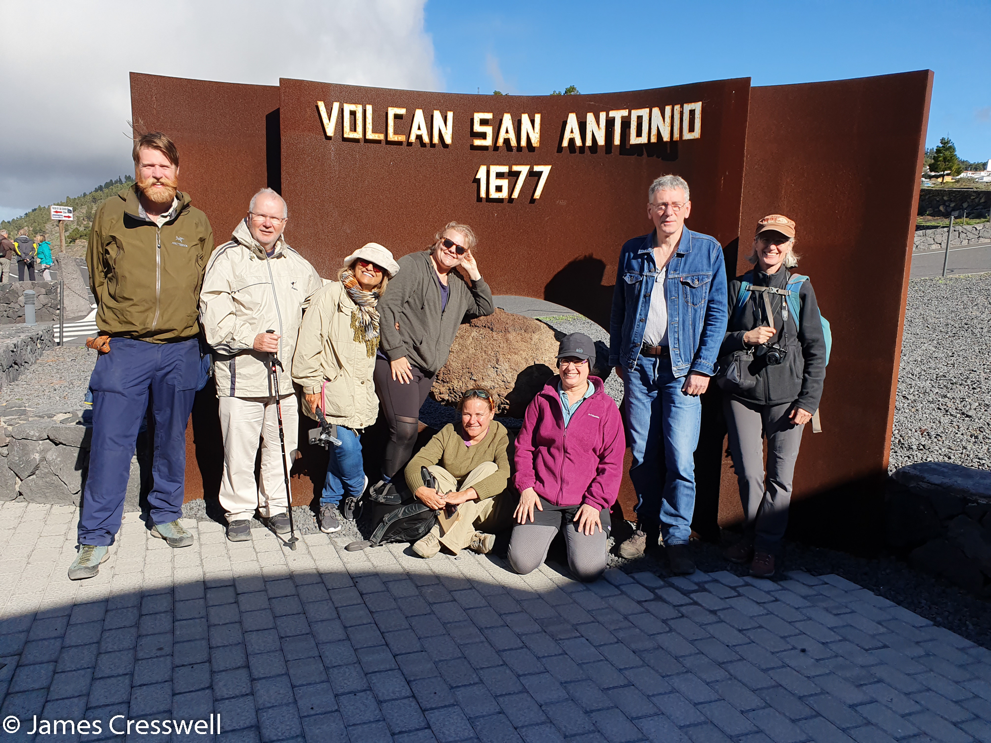 Group of people standing in front of metal sign
