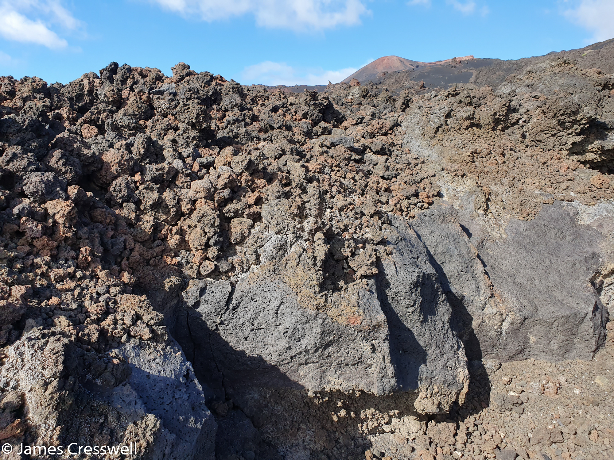 Solidified lava flow in the foreground with volcanic cone in the background