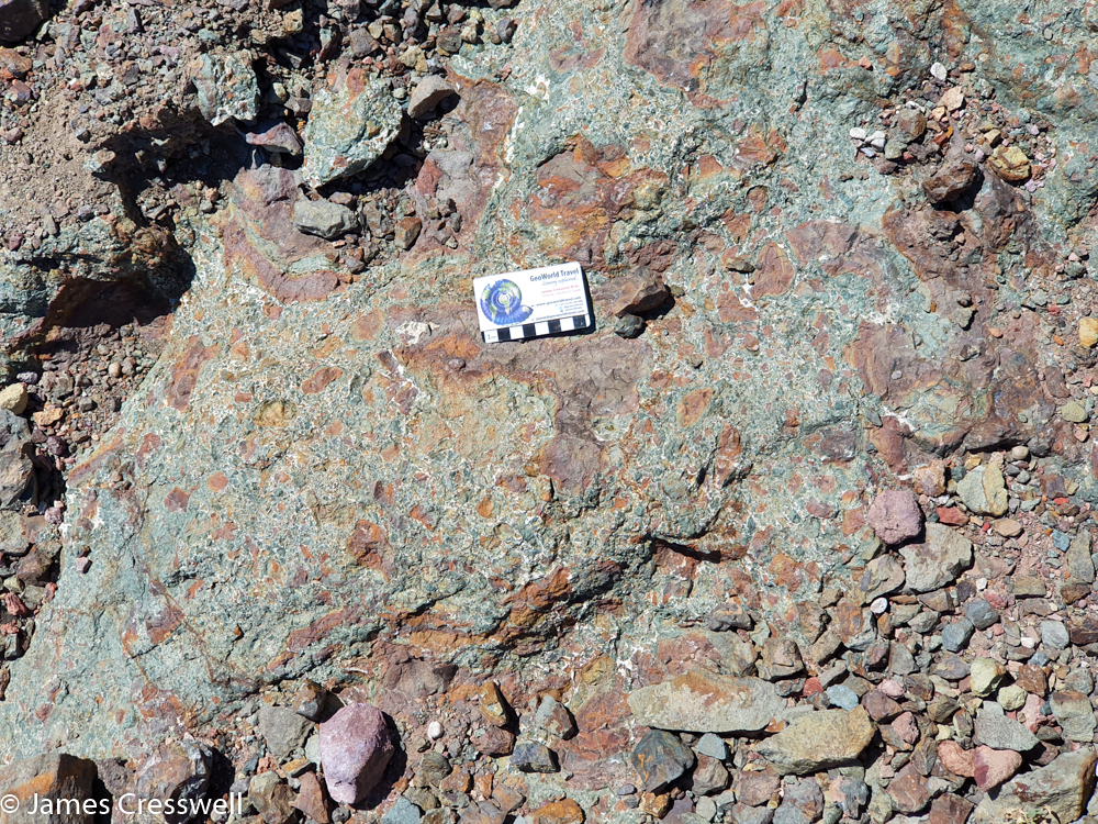A photograph of a a green coloured rock that has red blotches and a scale card