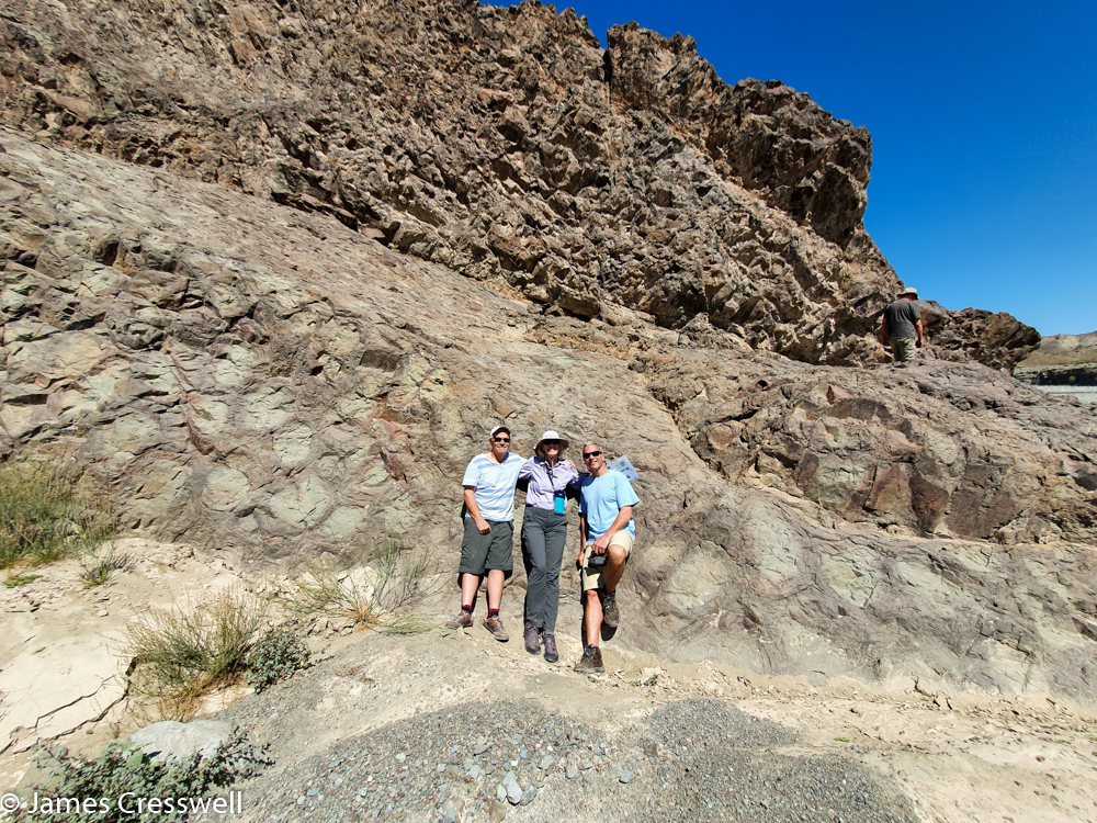 A photograph of a three people leaning ask a small cliff, that has circular patterns in the rock