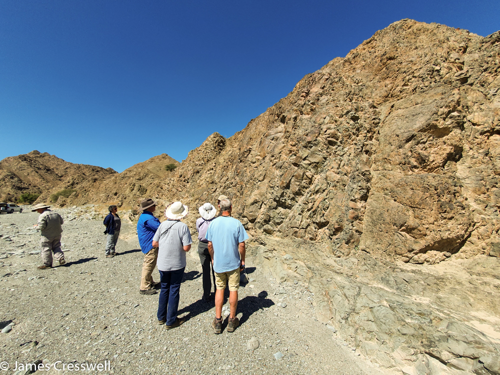 A photograph of a six people looking at a small rock cliff