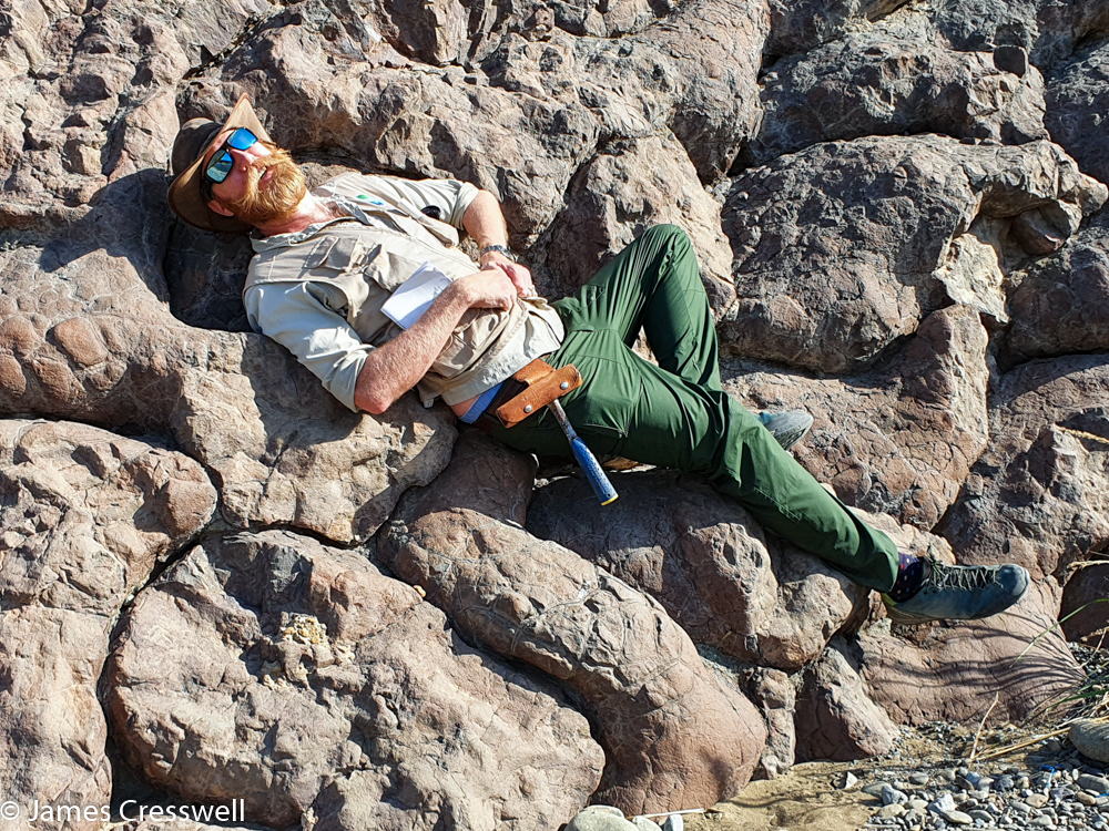 A man lying on his back on a hummocky rock surface