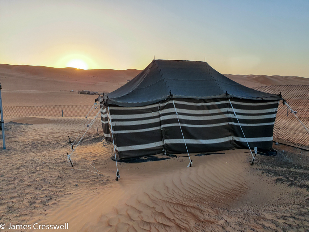 A photograph of a tent in the foreground, with the sun rising over sand dunes in the back ground