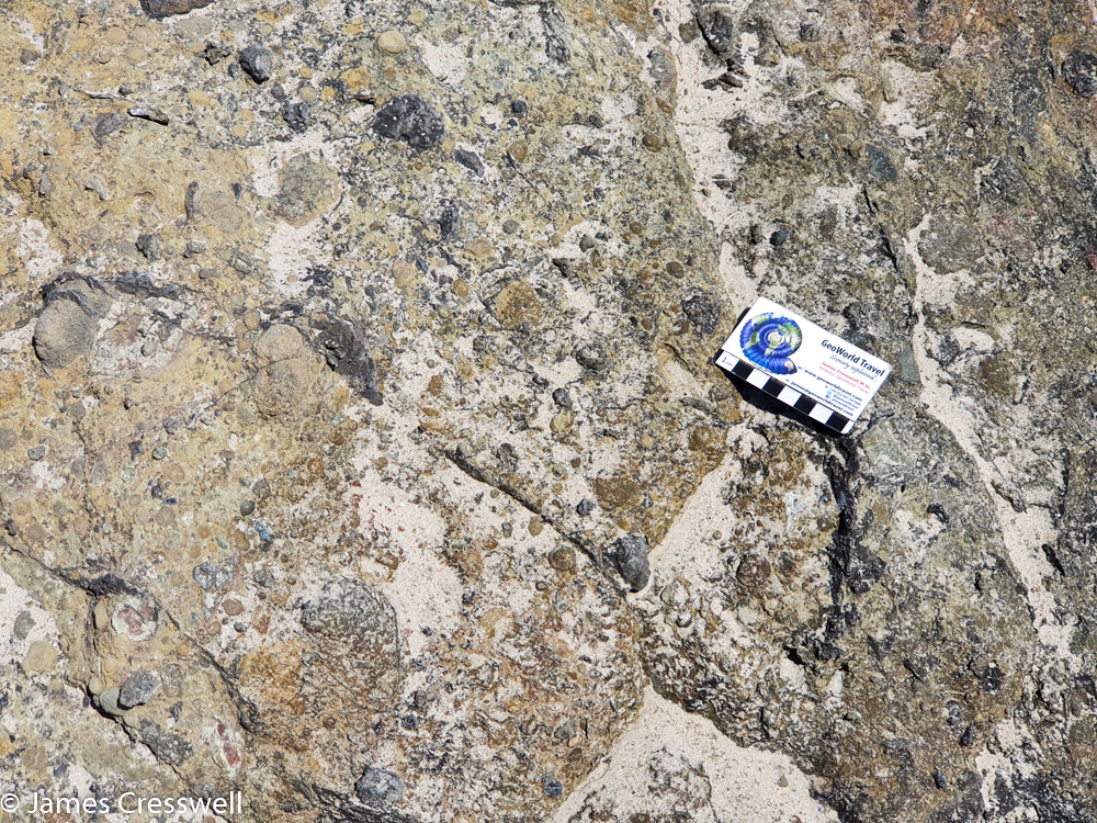 A scale card resting on a pale coloured rock rock surface