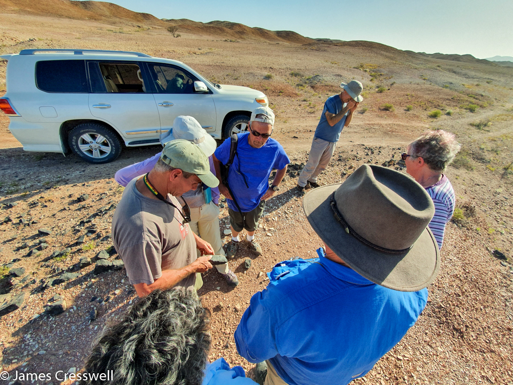 A photograph of a seven people talking about a rock, with a Landcruiser in the background