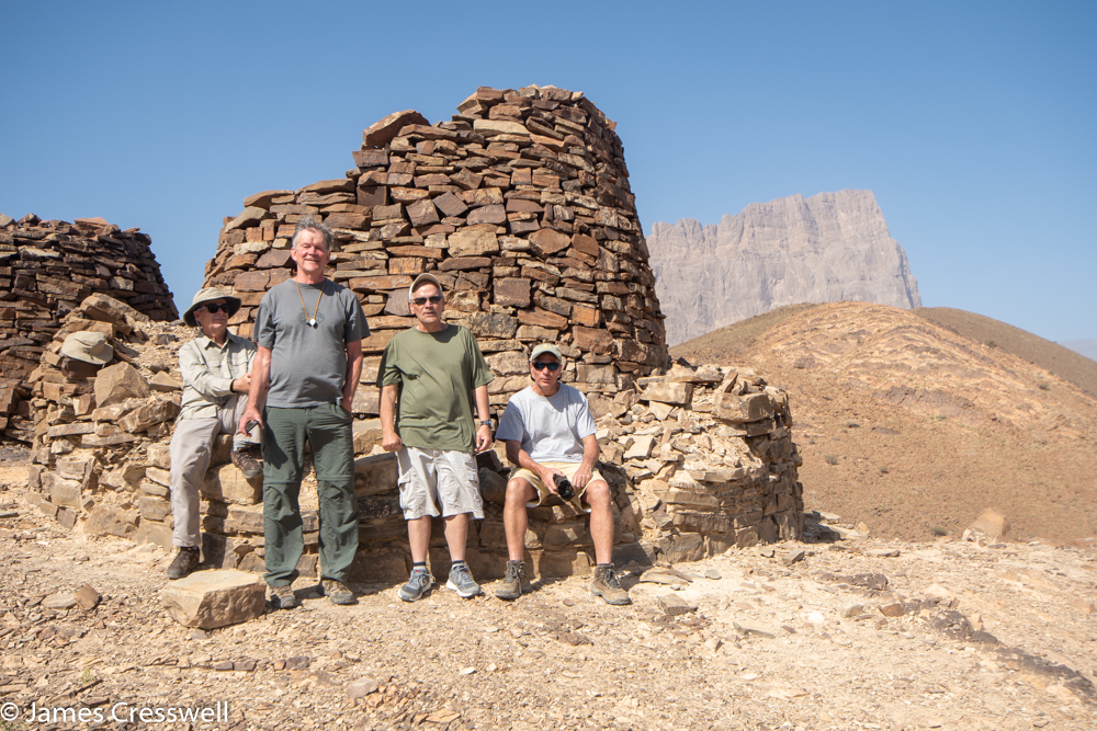 A photograph of four people in front of simple structure made from rocks