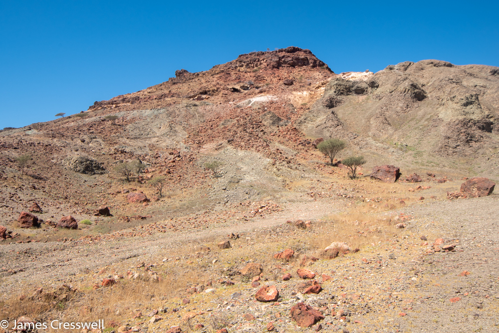 A photograph of a red coolured hill
