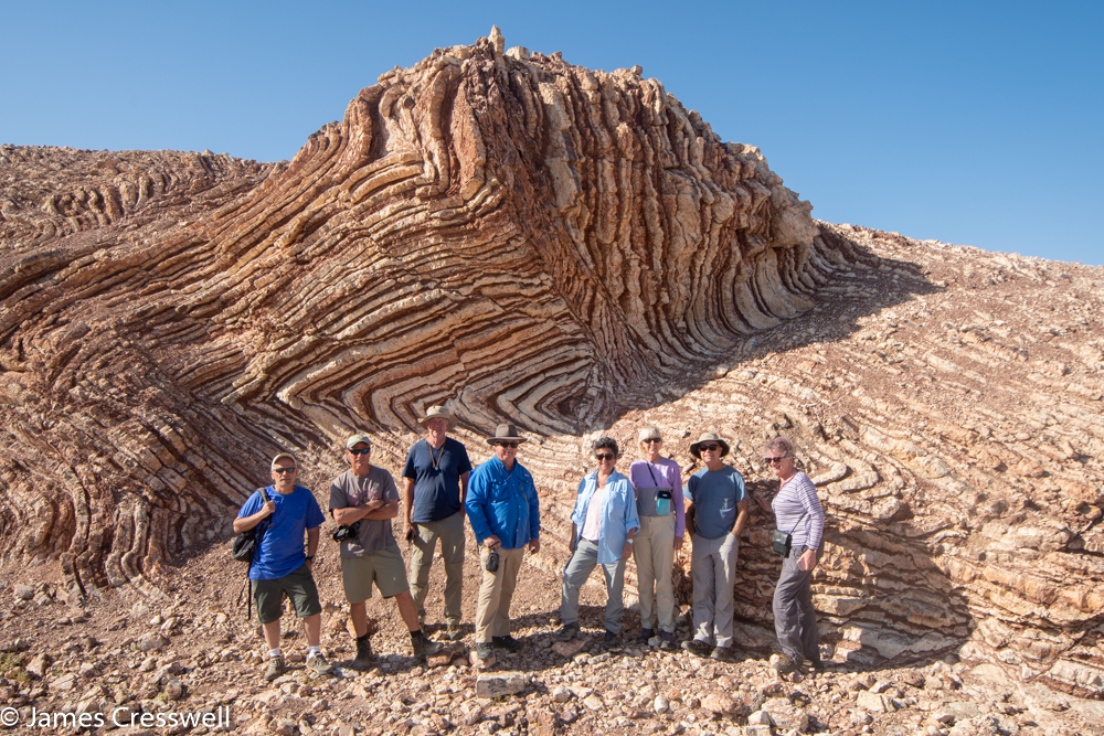 A photograph of a eight people standing in front of a small cliff that is made up of folded red and white layers
