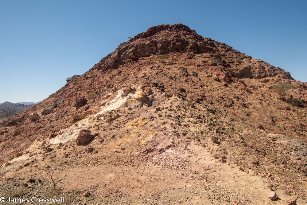 A photograph of a red hill top