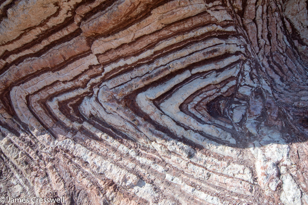 A photograph of a red and white striped rock in a sideways 'V' shaped fold