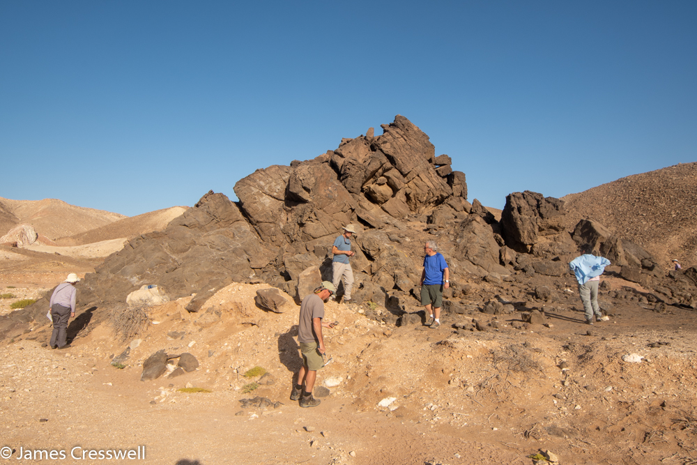 A photograph of a five people standing in front of a small grey hillock of rock