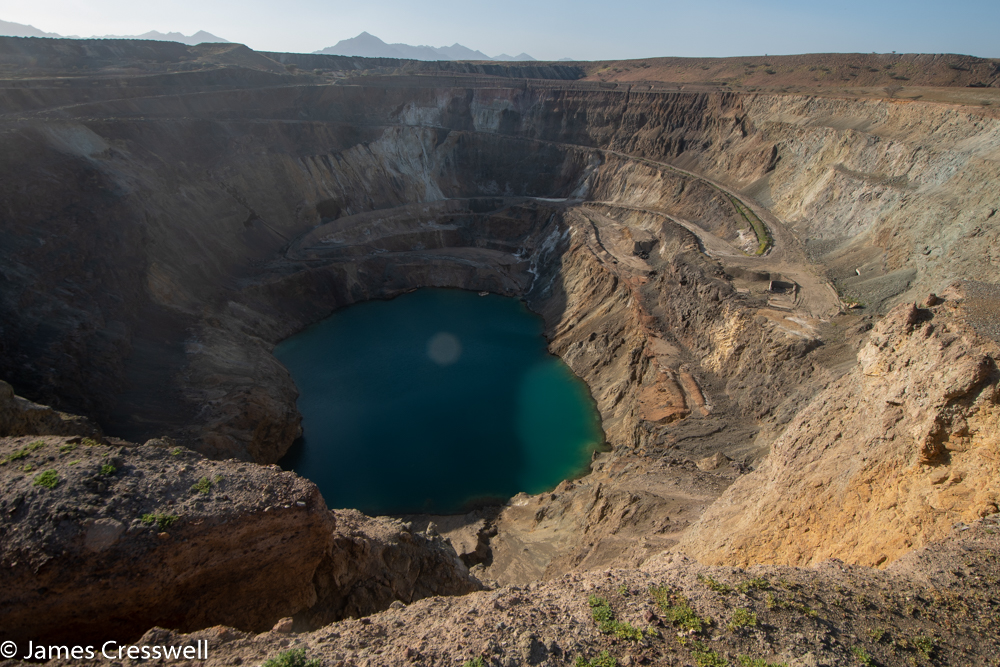 A photograph of a huge hole in the ground with a lake at its base
