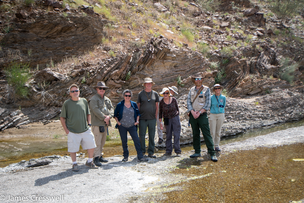 A photograph of a group of 8 people standing in front of a rock outcrop which has folded layers in it