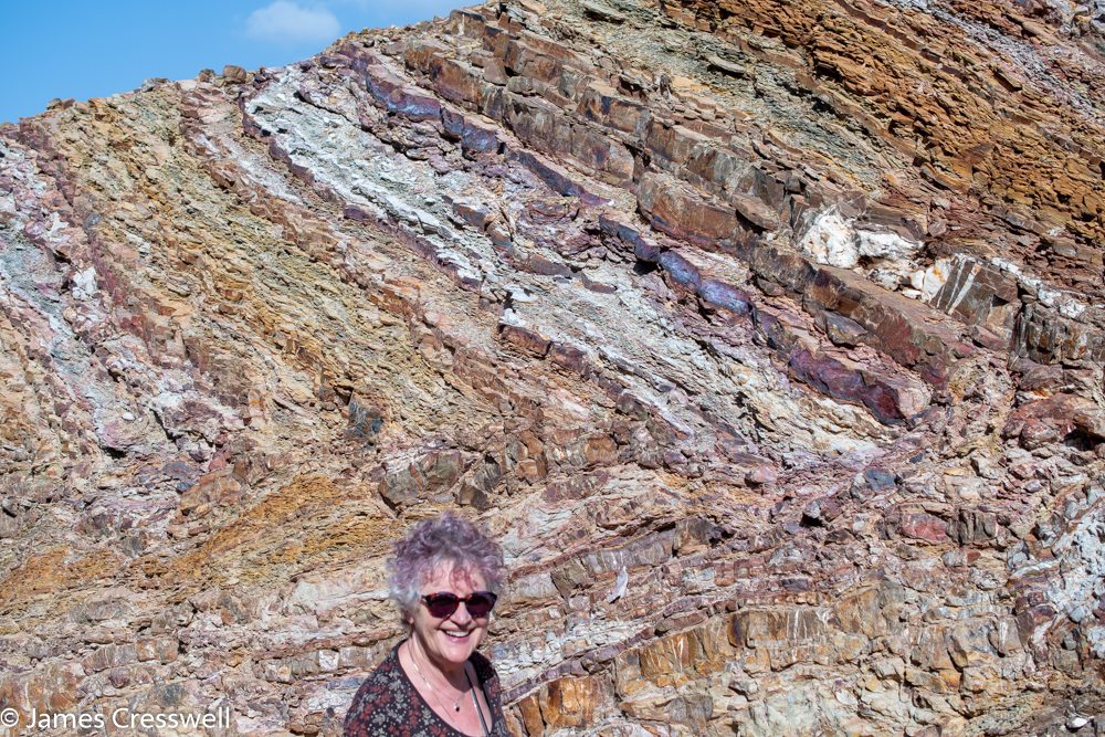 A photograph of a woman standing in front of a small cliff of rock that is multicolored