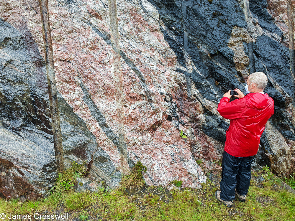 A man takes a photograph of colourful rocks