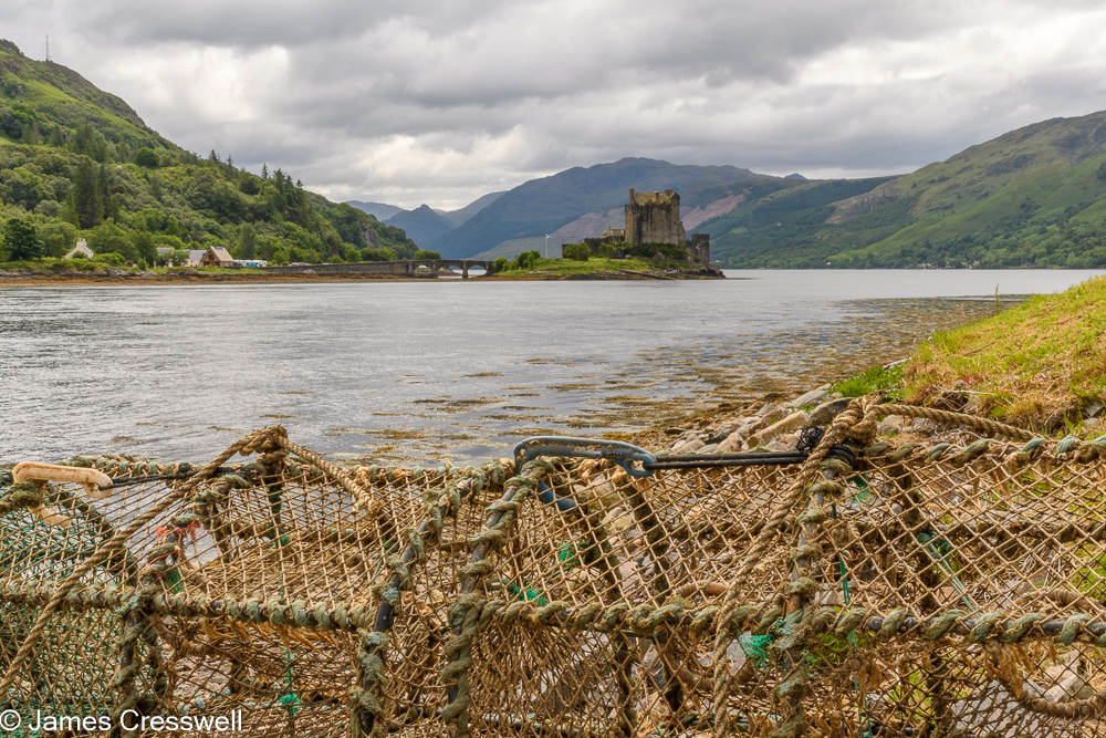 Lobster pots in the foreground with sea, a castle and mountains in the background