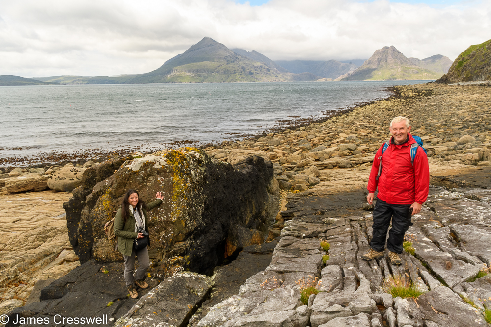 Two people standing on rocks with sea and mountains in the background