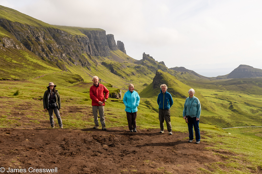 Five people standing in front an inland cliff