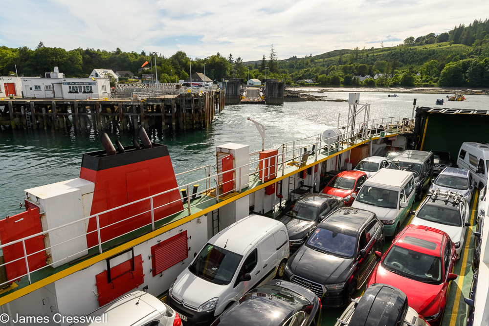 Looking down onto the deck of a ferry full of cars