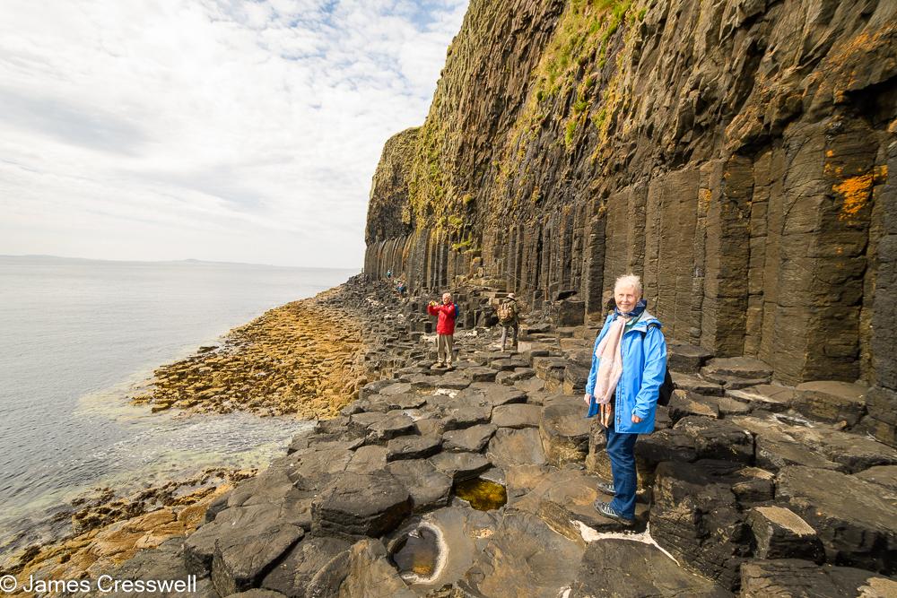 A woman stands on basalt columns, with a cliff of columnar basalt behind
