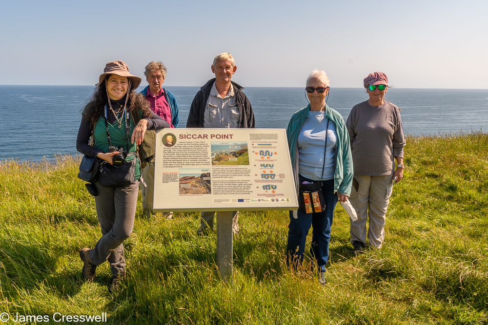 The 2021 GeoWorld Travel group standing next to the Siccar Point sign