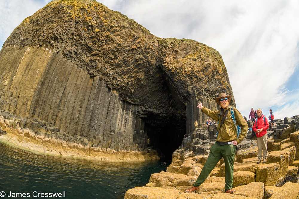 A man, James Cresswell, points to the entrance of a cave, Fingal's Cave