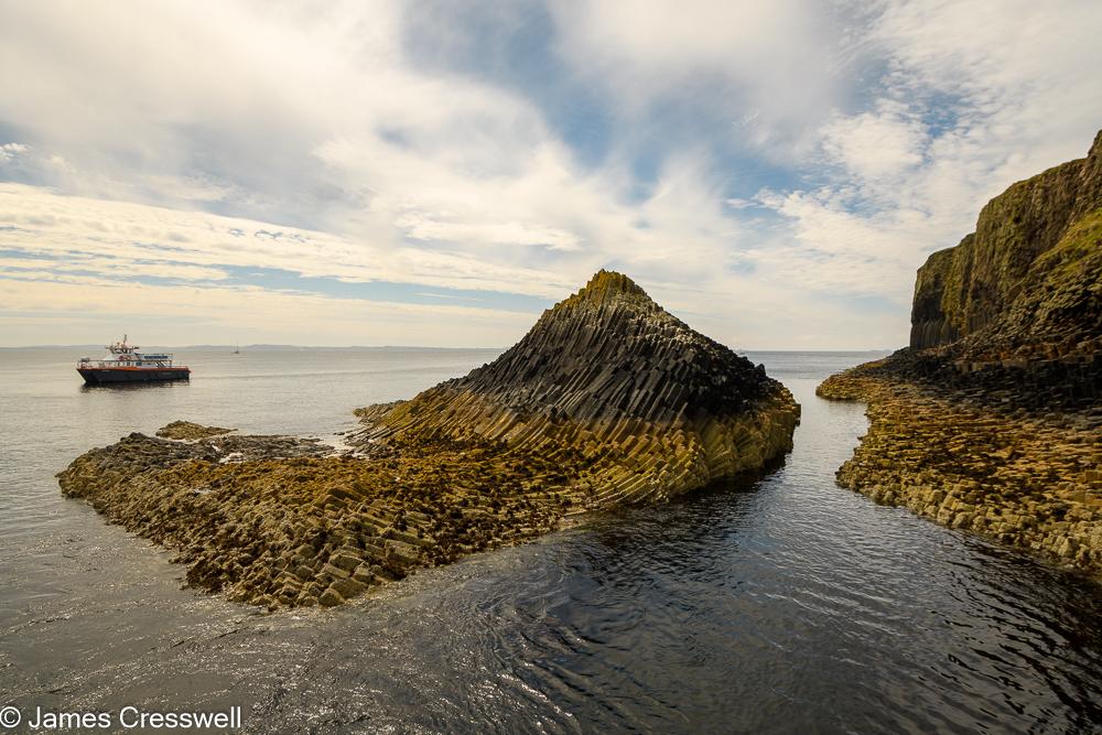 A shoreline with columnar basalt rocks and a boat