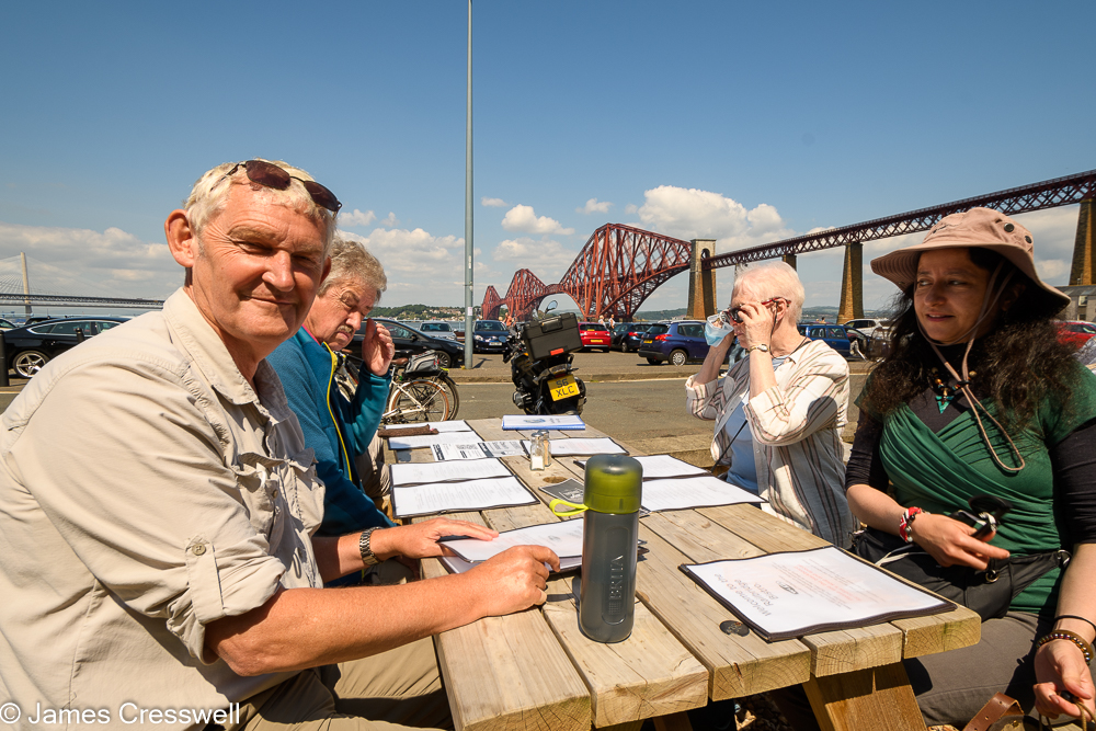 Four people sitting at a picnic table with a large red bridge in the background