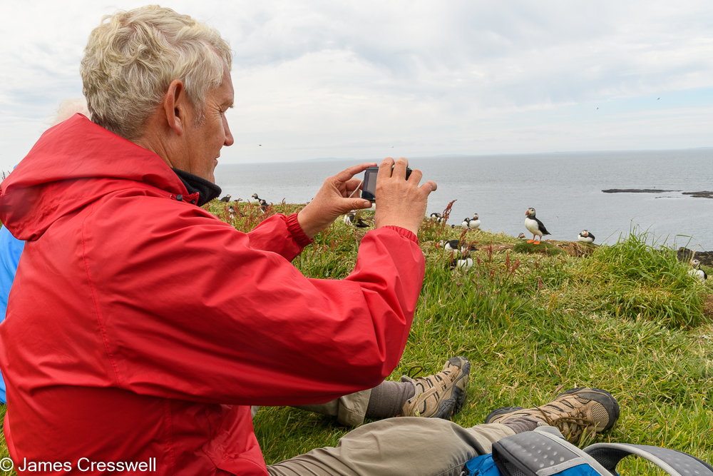 A man photographing puffins on the Isle of Lunga