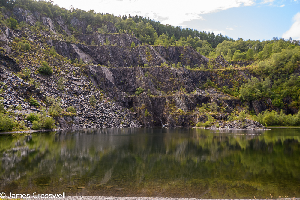 A pond with a quarry cliff face in the background