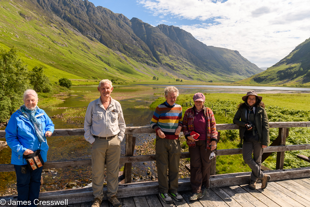 Five people stand on a bridge with a U shaped valley in the background