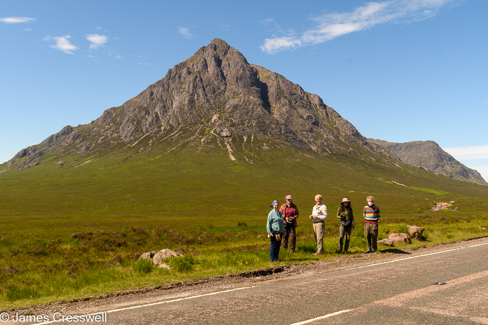 Five people stand in front of a cone shaped mountain